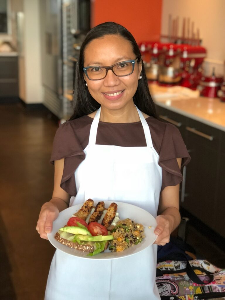 Be Meatless Youtube Channel  - Sally Mae holding a plate of vegan food at Uncorked Kitchen